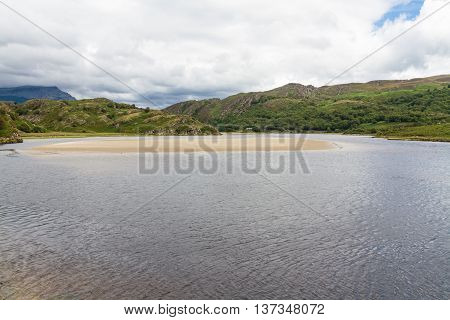 View of the River Dwyryd near Penrhyndeudraeth. Sand bank trees and rocky hills. Gwynedd Snowdonia Wales United Kingdom.
