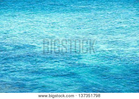 Beautiful clear blue waters of Okinawa coral reefs. Resort ocean water ripples.