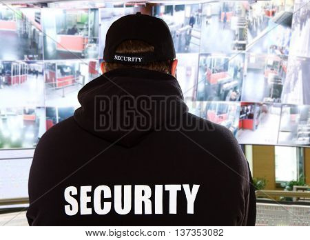 a security man looking into video monitor