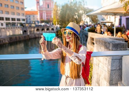Young female traveler making selfie photo with phone on the bridge in the center of Ljubljana city in Slovenia. Traveling Slovenia