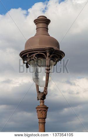 Parisian streetlamp, old against cloudy sky, France
