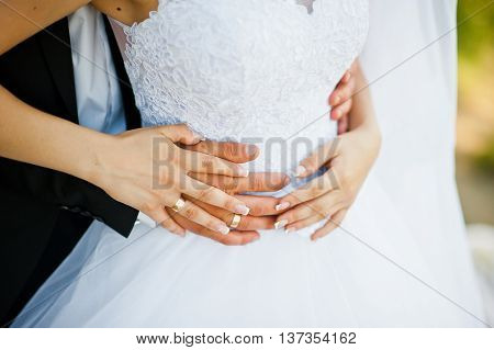 hands of wedding couple with rings at wedding day