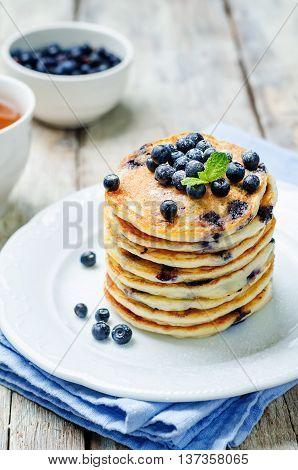 Blueberry Ricotta Pancakes on white wood background.