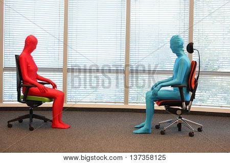 anonymous couple in full body  elastic suits sitting on armchairs in sunny space
