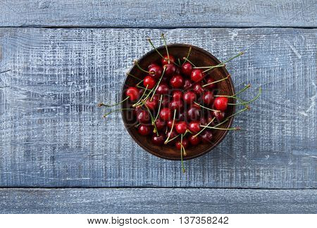 Sweet fresh cherries in a bowl on blue rustic wood closeup, fruit backround. Healthy food top view with copy space
