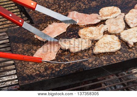 Barbecue pork chops and chicken on a hot granite countertop. Summer party with barbecue. Grilling on a hot stone.