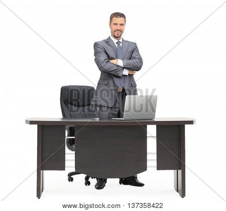 Handsome businessman standing next to the table isolated on white background