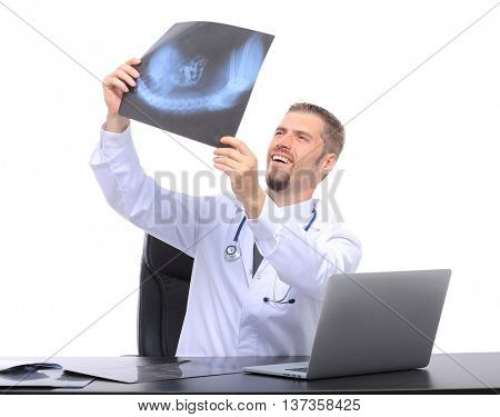 smiling male doctor sitting at table with x-ray results and stethoscope over white background