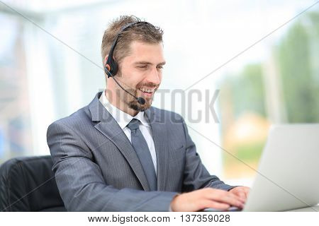 Portrait of handsome employee working at his desk with headset and laptop. Callcenter.