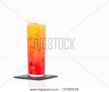 Tropical cocktail known as a tequila sunrise in a tall glass.
