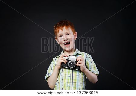 Little cute boy pose with old vintage film camera at black background. Small redhead child photographer happy and laughing, studio portrait
