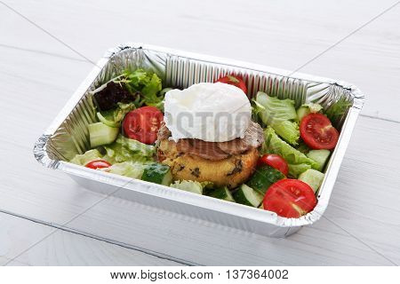 Restaurant food delivery in foil box on white wood table. Poached egg closeup on veil steak medium rare with fresh vegetable salad and couscous cushion. Dish take away closeup, healthy meal.
