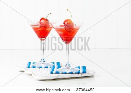 Fruity summer cocktail topped with a fresh whole cherry.
