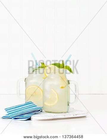 Two jars filled with ice cold homemade lemonade.