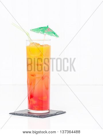 Tropical cocktail known as a tequila sunrise in a tall glass with ice.