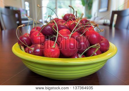 Pile of Bing Cherries in green bowl and on wood dining table