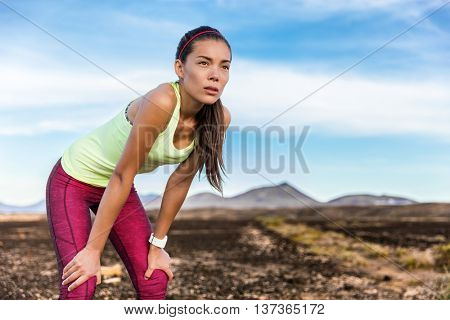 Tired trail running woman looking at mountain landscape nature path with focus and determination to take on weight loss cardio goal achievement challenge. Asian sports athlete runner breathing.