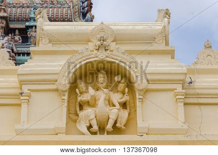 Tamil Nadu India - October 18 2013: Cream-colored statue of Lord Murugan and his two wives sitting on the peacock at Pillayarpatti Karpaga Vinayagar temple entrance.