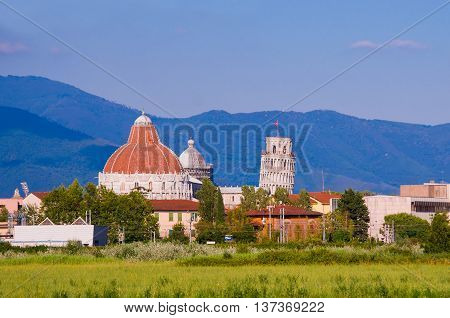 It is seen as the Leaning Tower of Pisa and the cathedral domes and the baptistery arriving in Pisa from the countryside