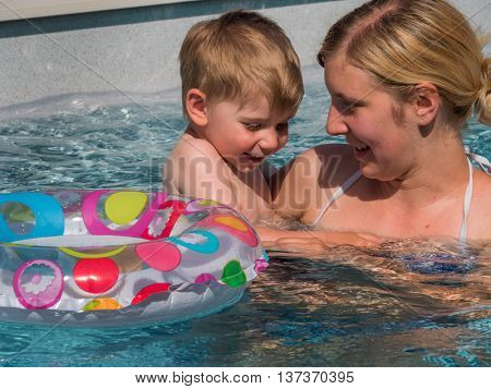child with floating ring cools off in the pool on hot day at the