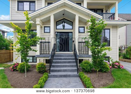 Entrance of a luxury house with beautiful landscaping on a bright sunny day.