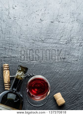 Wine bottle, wine glass and corkscrew on the graphite board.