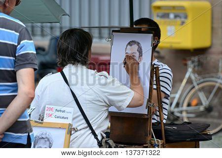 Strasbourg, France - July, 2012: Unidentified French artist draws an unidentified boy. Editorial.