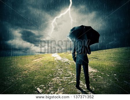 Man with umbrella on a field during the storm