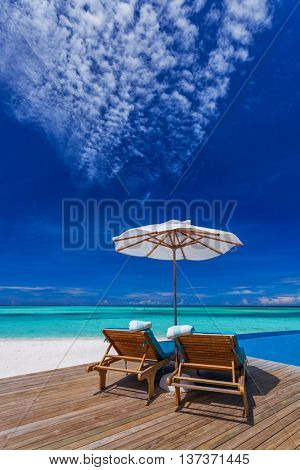 Sun umbrellas and wooden beds on tropical beach with the best view over the pool