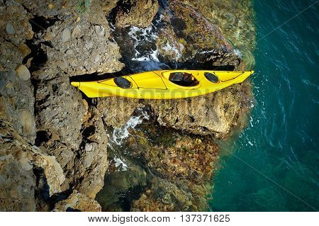 yellow sea kayak beached on a rocky rapids and blue water