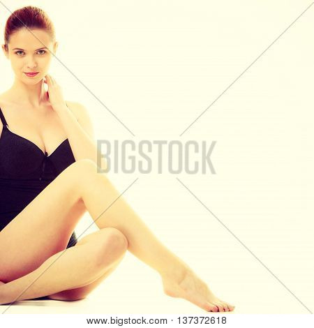 Beautiful slim healthy woman body wearing black cotton underwear. Attractive red haired female posing. Studio shot toned image