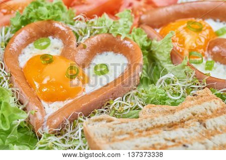 Heart shaped sausages with fried eggs. Home made breakfast