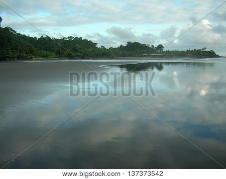 Sky reflected in receding water on long, wide beach at Almejal, Colombia.