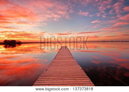 Fishing dock at sunrise with beautiful pink and orange clouds