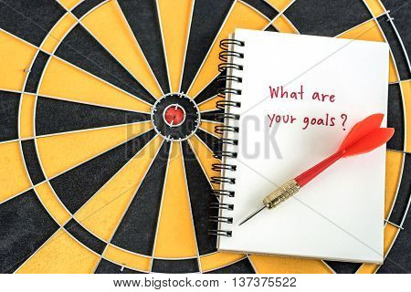 Red dart target arrow on open notebook with alphabet letters hand writing word what are your goals and question mask over dartboard background Marketing concept