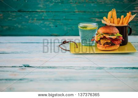 Tasty street food grilled beef burger in crispy shortbread with lettuce and mayonnaise served on small cutting board a rustic wooden table with copyspace