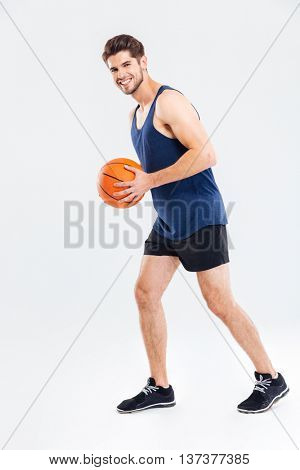 Full length portrait of a young sports man playing in basketball isolated on a gray background