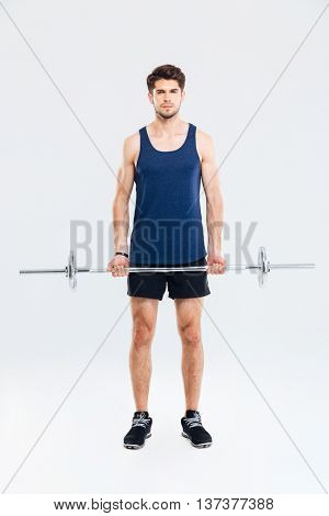 Ful length of serious young man athlete standing and holding barbell over white background