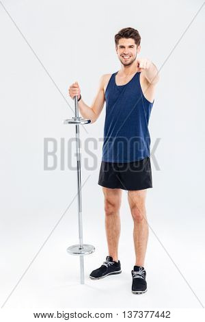 Young handsome sportsman holding barbell and pointing finger at camera isolated on a gray background