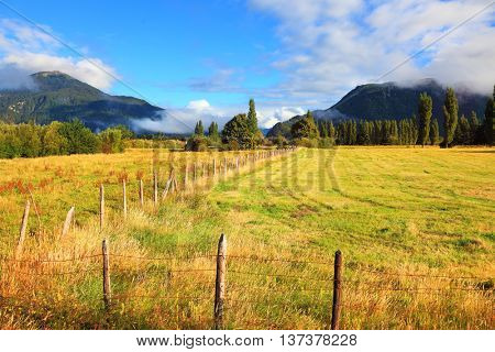 Green field fenced low fence. Mountain range is visible in the distance. Countryside in Chilean Patagonia