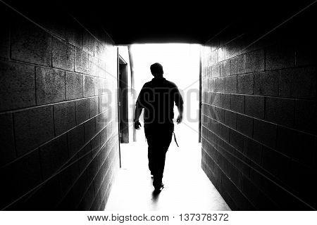 Man Walks Down Dimly Lit Outdoor Hallway