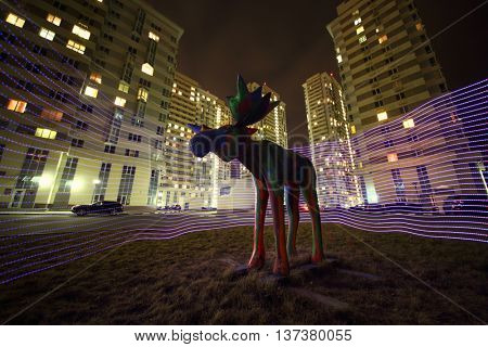 MOSCOW - MAR 28, 2015: Wooden sculpture of a moose in the neon lighting in the courtyard of a residential complex of Elk Island in the dark time