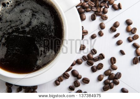 White cup with coffee and coffee seed on the table