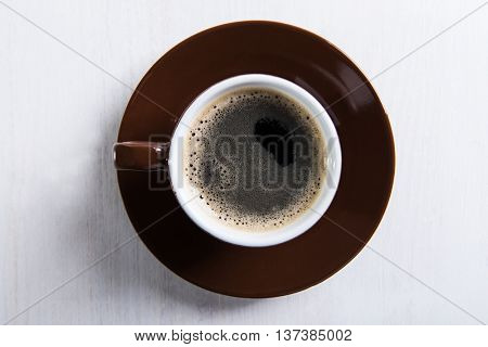 Brown cup with coffee on the table