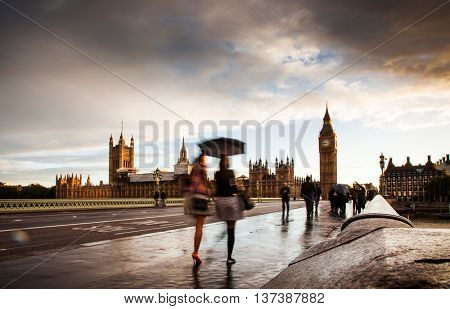 Big Ben at sunset on a rainy day, blurred people with umbrellas, Westminster, London, UK