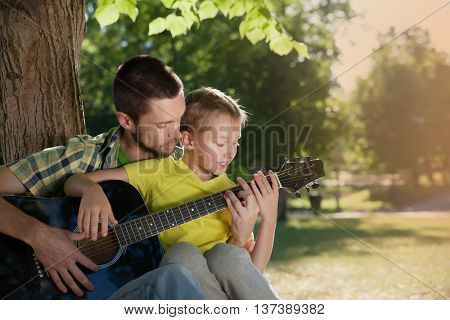 father learning his boy to play guitar
