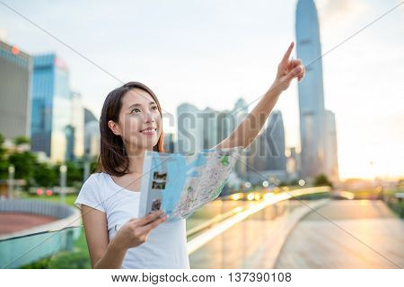 Woman using city map and finger pointing far away