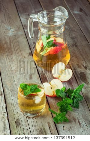 Glass and carafe of green tea with mint and apples