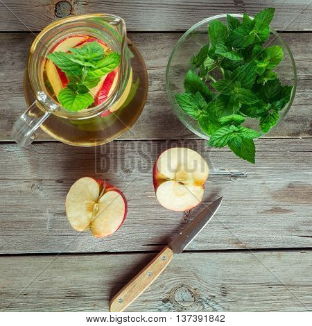 Decanter cool green tea with mint and cut apple flat lay