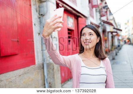Woman taking selfie by smart phone in Rua da felicidade